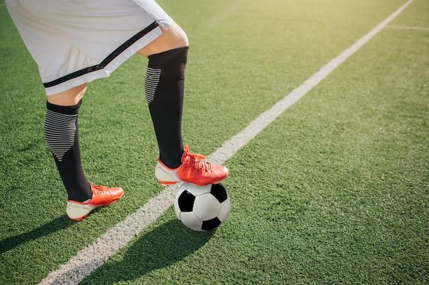 Foto van onderste deel van lichaam voetballer. hij staat op het groene veld en houdt een been op de bal. witte lijn komt over groen gazon.