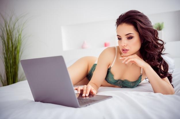 Foto van ondeugende thuiswerker op afstand dame in quarantaine online laptop chat uitkleden scherm privé show fit lichaam voor geld chatten vip klant dragen bikini liggend lakens linnen slaapkamer binnenshuis