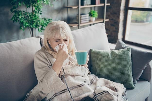 Foto van ongelukkig blond oud oma betrapt koud niezen servet drinken hete thee drank zittend sofa divan bedekt geruite deken woonkamer binnenshuis