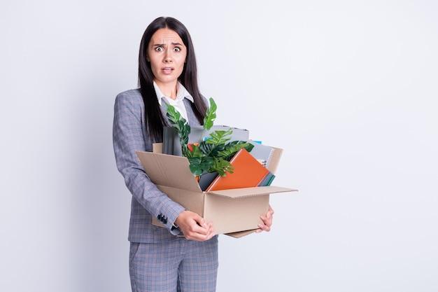 Foto van ongelukkig verrast wanhopig ontslagen dame ondervraagd gezicht niet geloven tijdperken verloren werk baan recessie personeel houden kartonnen doos pack bezittingen formalwear geïsoleerde grijze kleur achtergrond