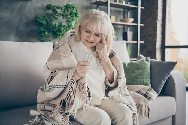Foto van ongelukkig witharige oude oma die pijnstiller pillen houdt, kan niet tegen vreselijke hormonale migraine zitten sofa divan bedekt geruite deken woonkamer binnenshuis