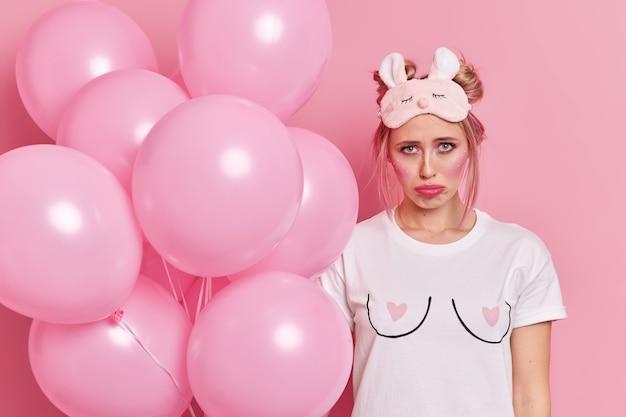 Foto van ongelukkige blonde vrouw met lichte make-up heeft sombere uitdrukking