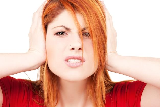 Foto van ongelukkige roodharige vrouw met handen op oren