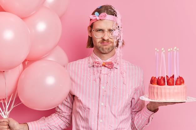 Foto van ongelukkige verjaardag jongen heeft een slecht humeur op partij houdt heerlijke cake en een heleboel helium ballonnen