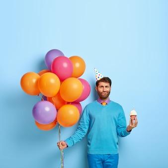 Foto van ongeschoren man met verjaardagshoed en ballonnen poseren in blauwe trui