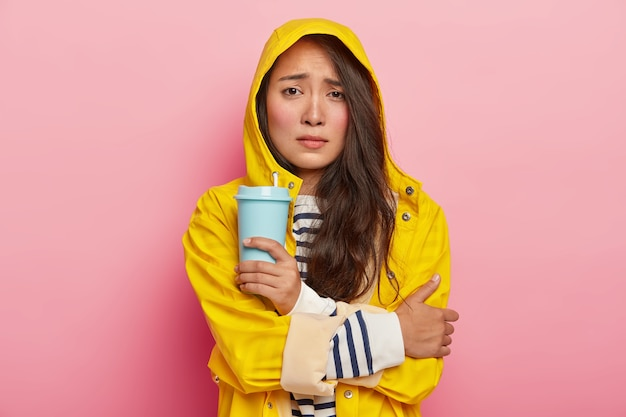 Foto van ontevreden aziatische vrouw grijnst gezicht, houdt de armen gekruist, beeft van het koud zijn na een wandeling in de regen, draagt gele regenjas, houdt afhaalmaaltijden koffie, verwarmt zichzelf met warme drank