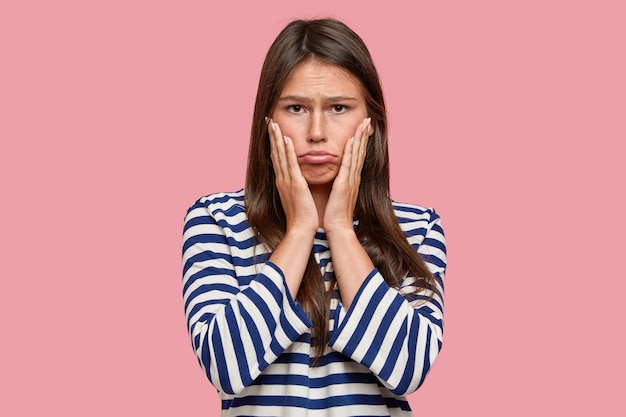 Foto van ontevreden blanke tiener portemonnees lippen, houdt beide handen op de wangen