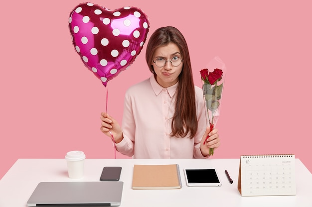Foto van ontevreden brunette dame fronst gezicht van ontevredenheid, draagt valentijn en boeket rozen, boos om cadeau te ontvangen van vreemdeling, poseert op bureaublad met blocnote