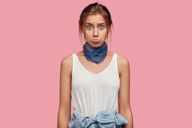 Foto van ontevreden jonge vrouw met bril poseren tegen de roze muur