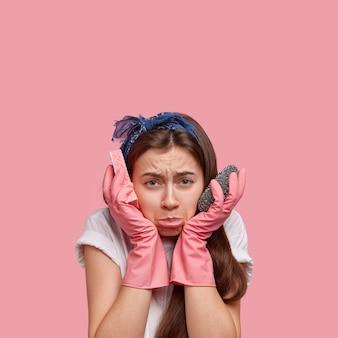 Foto van ontevreden jonge vrouw met onderlip, donker lang haar, voelt zich overwerkt na de voorjaarsschoonmaak thuis