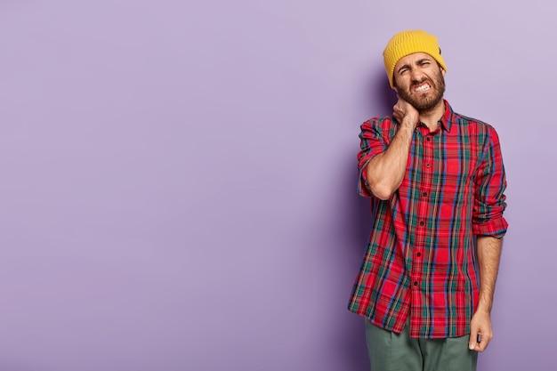 Foto van ontevreden jongeman met borstelharen, voelt stijfheid in nek, kantelt het hoofd, klemt tanden, gekleed in een geruit overhemd, staat tegen paarse achtergrond lege ruimte voor uw promotionele inhoud
