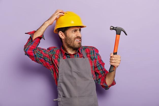 Foto van ontevreden klusjesman draait naar rechts, kijkt in de verte met fronsend gezicht, houdt hamer vast, is professionele bouwer, ziet nieuw object voor reparatie draagt helm, schort. renovatie, engineering