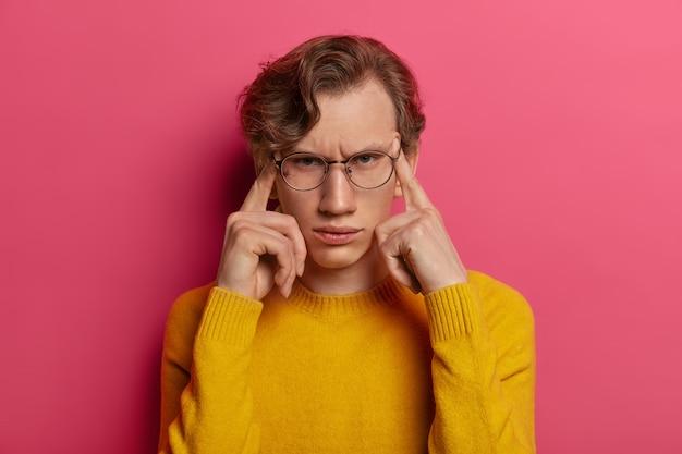 Foto van ontevreden man lijdt aan hoofdpijn, fronst gezicht, raakt slapen aan met vingers, probeert zich te concentreren, herinnert zich iets, draagt een bril, gele trui, geïsoleerd op roze muur