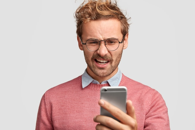 Foto van ontevreden man student houdt slimme telefoon, kromt lippen, leest negatief nieuws op internet, ziet vreselijke foto's
