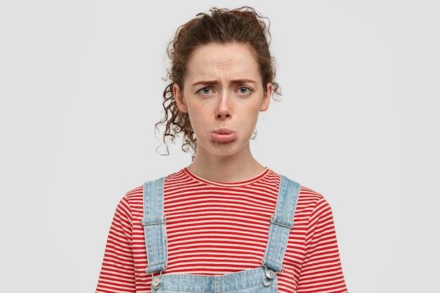 Foto van ontevreden neerslachtige vrouw tuitte lippen, fronst gezicht, heeft de dag op de universiteit bedorven