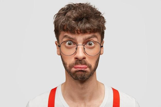 Foto van ontevreden ongeschoren man portemonnees onderlip, heeft donker haar, kijkt verbijsterd naar de camera