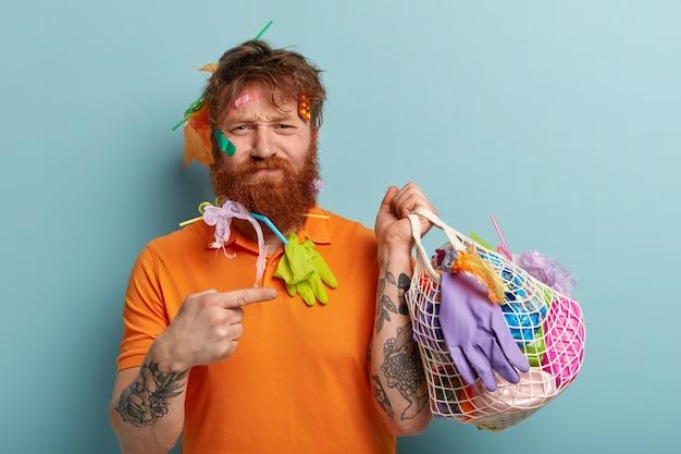 Foto van ontevreden roodharige man met dikke haren, wijsvinger wijst naar zak gevuld met plastic afval, draagt casual oranje t-shirt, heeft getatoeëerde arm, staat over blauwe muur. dag van de aarde