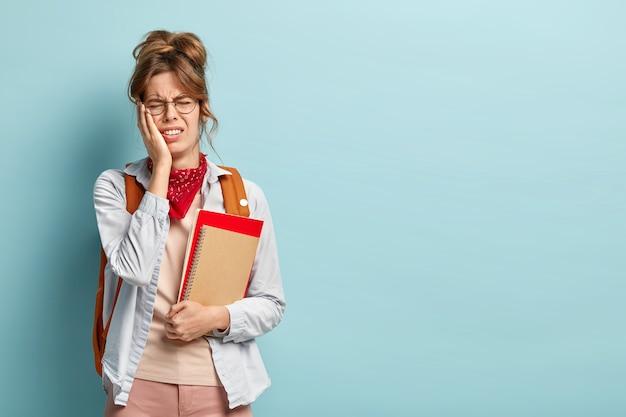 Foto van ontevreden stressvol moe schoolmeisje draagt spiraalvormige blocnote en boek, draagt een ronde bril