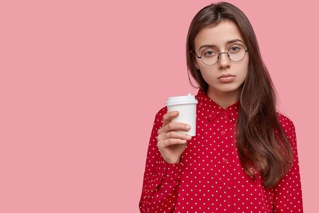 Foto van ontevreden trieste vrouw drinkt koffie, heeft slaperige uitdrukking, geniet van vers drankje