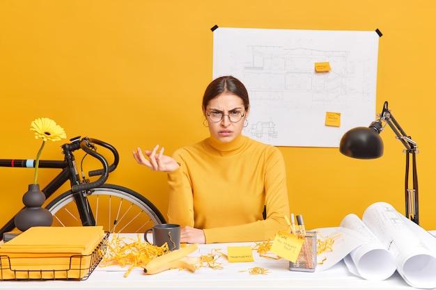 Foto van ontevreden verontwaardigde vrouwelijke kantoormedewerker haalt schouders op, weet niet hoe hij projectwerk moet afmaken. vrouwelijke studentontwerper werkt aan tekeningen, poses in coworking-ruimte. onderwijs concept