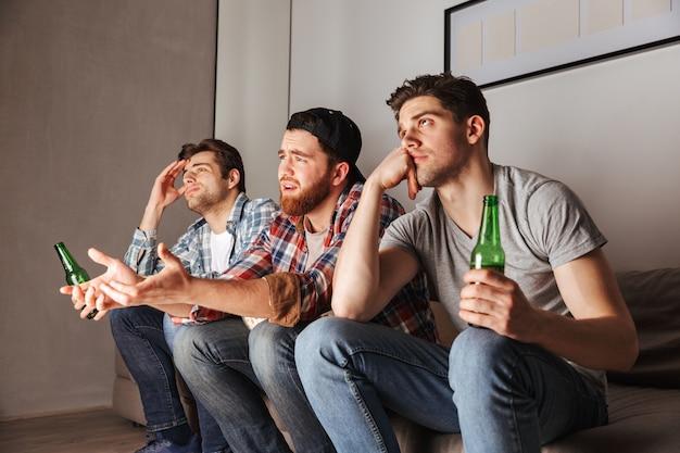 Foto van ontevreden volwassen mannen die frustratie uiten, zittend op de bank en kijken naar voetbalwedstrijd in appartement
