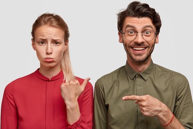 Foto van ontevreden vriendin heeft ruzie met vriendje, draagt rode blouse, wijst met duim naar vrolijke man, houdt niet van iets. positieve blanke man maakt grapjes over mooi meisje, binnen staan