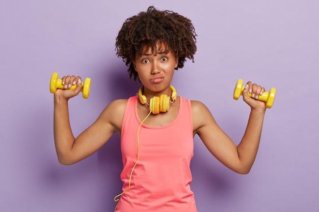 Foto van ontevreden vrouw met krullend borstelig haar, bezig met biceps-oefeningen, luistert ongewild coach, heft armen met halters, draagt casual roze vest