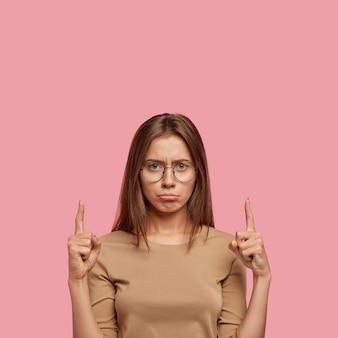 Foto van ontevreden vrouw portemonnees onderlip, gelaatsuitdrukking heeft ontevreden, ontevreden