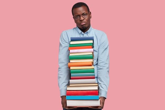 Foto van ontevreden zakenman met donkere huid houdt stapel wetenschappelijke boeken vast, heeft een ongelukkige gezichtsuitdrukking, draagt een formeel shirt en bril, geïsoleerd over roze studiomuur