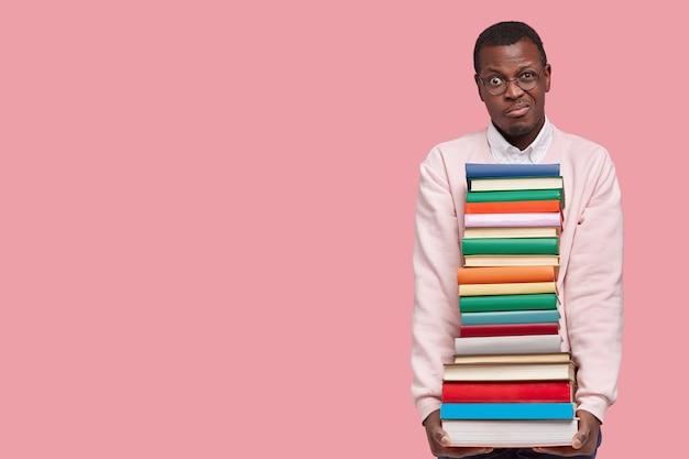 Foto van ontevreden zwarte student houdt zware stapel leerboeken vast, kijkt ongenoegen, bereidt zich voor op onderzoek