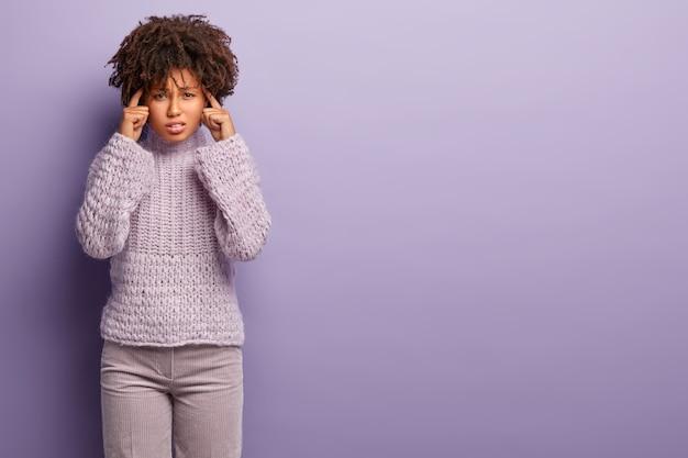Foto van ontevredenheid donkere vrouw houdt de handen op de slapen, lijdt aan migraine, pijnlijke gevoelens, draagt een gebreide trui en broek, probeert zich ergens op te concentreren. vrije ruimte voor uw tekst