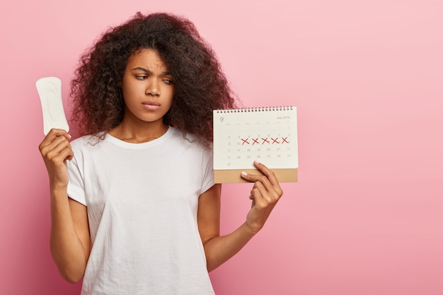 Foto van ontevredenheid mooie gekrulde vrouw kijkt naar kalender met gemarkeerde pms-dagen