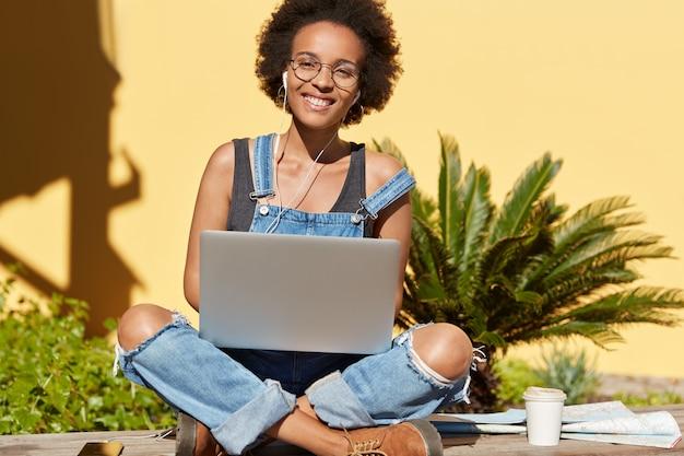 Foto van ontspannen zorgeloze donkere vrouw zit gekruiste benen, surft internetwebsite op laptopcomputer, geniet van vers drankje, luistert aangenaam audiotrack met oortelefoons. afro-amerikaanse blogger