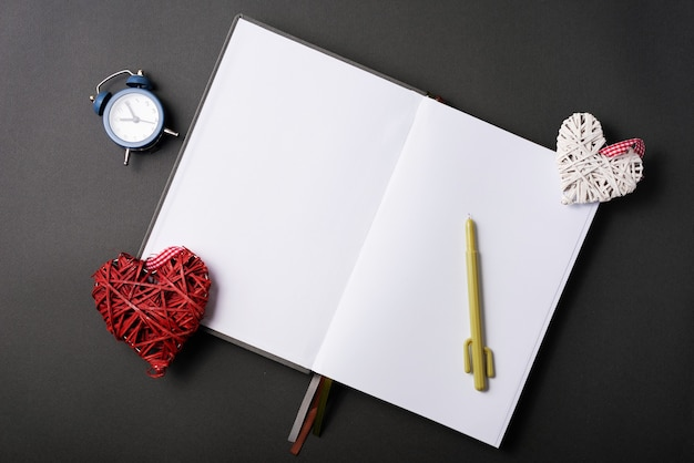 Foto van open leeg dagboek met klok en geslepen harten over zwarte lijst
