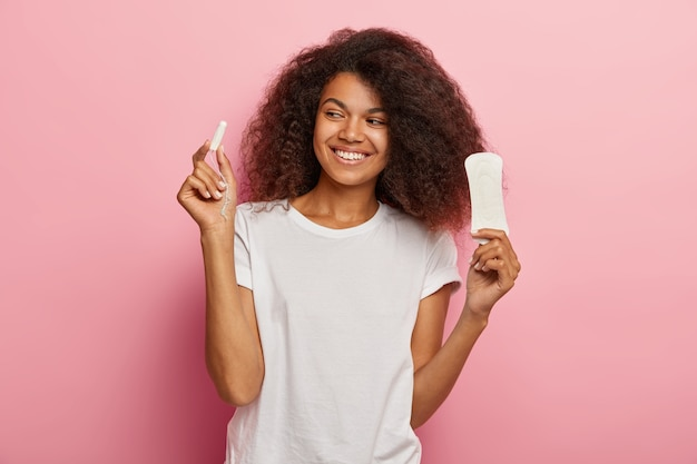 Foto van opgetogen afro-amerikaanse vrouw houdt tampon en maandverband, gekleed in witte t-shirt, geïsoleerd over roze muur. vrouwen, pms