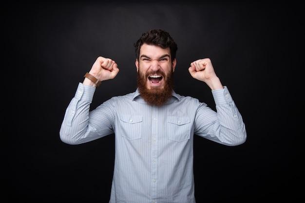 Foto van opgewonden bebaarde man, schreeuwen en vieren met armen omhoog over donkere geïsoleerde achtergrond