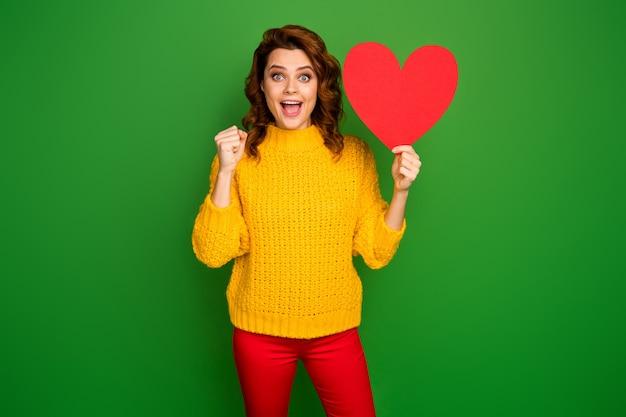 Foto van opgewonden gekke dame houd papier hartvorm briefkaart vriendje uitnodiging voor romantiek date prom slijtage gele gebreide trui rode broek geïsoleerde helder groene kleur muur