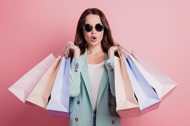 Foto van opgewonden geschokte jonge brunette vrouw met koopjes om te winkelen