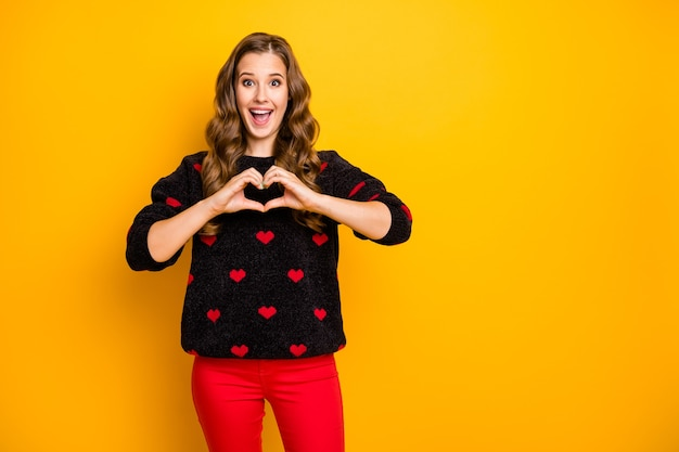 Foto van opgewonden grappige krullende dame uitnodigende vriend romantische date met armen hart vorm figuur dragen zwarte rode harten patroon trui broek