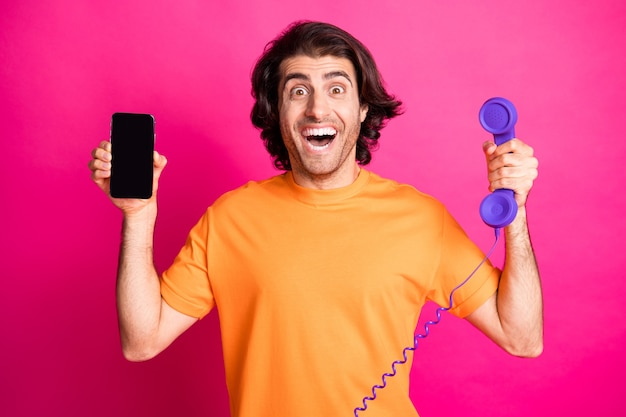 Foto van opgewonden man met open mond houd telefoon smartphone scherm lege ruimte draag oranje t-shirt geïsoleerde roze kleur achtergrond