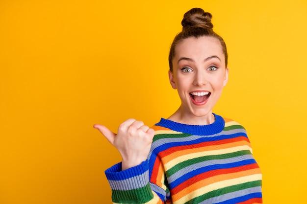 Foto van opgewonden meisje promotor punt duim vinger copyspace onder de indruk ongelooflijk adverteren promotie keuze besluit advies draag trui geïsoleerd over glans kleur achtergrond