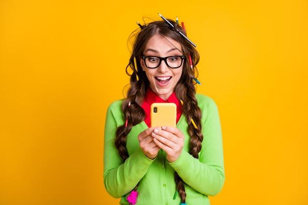 Foto van opgewonden nerd meisje las college examen nieuws smartphone geïsoleerde gele kleur achtergrond