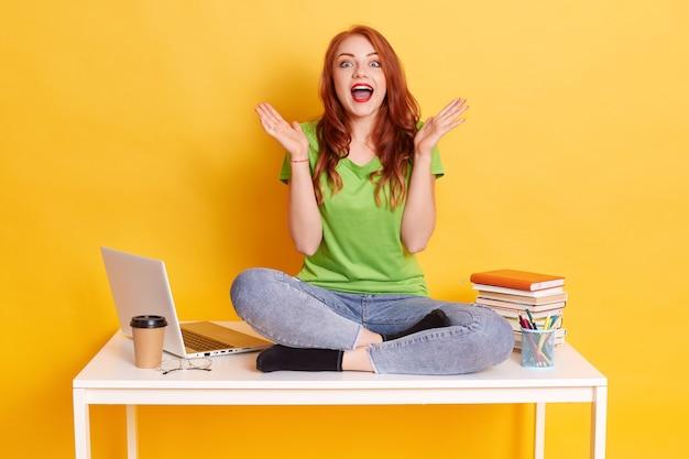 Foto van opgewonden studentenmeisje zittend aan een bureau omringd met schriften, laptop, koffie, mond wijd openhoudend met handpalmen opzij, geïsoleerd op gele achtergrond.