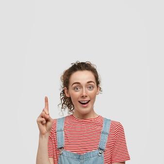 Foto van opgewonden verrast vrouw met sproeten huid, punten met wijsvinger, toont iets geweldigs naar boven