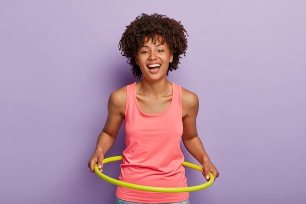 Foto van optimistische donkere vrouw draait hoepel hoepel, streeft naar een perfecte taille