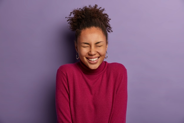Foto van optimistische gekrulde vrouw met donkere huid, sluit de ogen en glimlacht breed, toont witte tanden, voelt zich dolgelukkig, drukt goede emoties uit, hoort hilarische grap, geïsoleerd over paarse muur