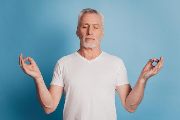 Foto van oude man mediteren om teken geïsoleerd op blauwe achtergrond