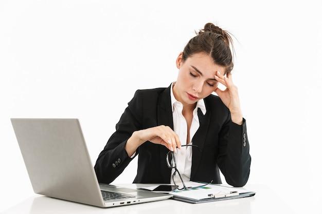 Foto van overwerkte vrouwelijke werkneemster, gekleed in formele kleding, zittend aan een bureau en werkend op een laptop op kantoor geïsoleerd over een witte muur