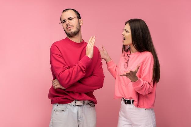 Foto van paar debatteert en kijkt samen ongelukkig, geïsoleerd over roze achtergrond.