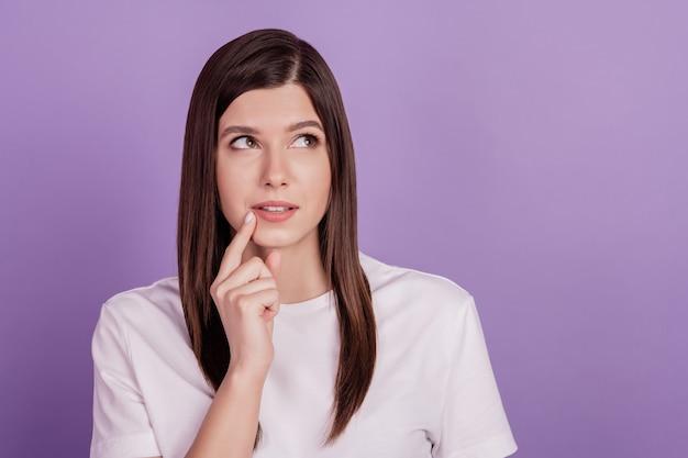 Foto van peinzende dame die op zoek is naar lege ruimte denkende arm op kin geïsoleerd op violette achtergrond